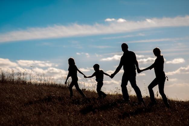 Schattenbild, gruppe der glücklichen familie spielend auf wiese, sonnenuntergang, sommerzeit Premium Fotos