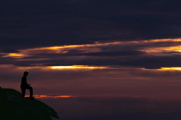 Schattenbild-mann, der auf berg gegen himmel während des sonnenuntergangs steht Premium Fotos