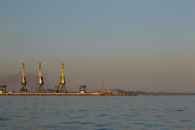 Schattenbild vieler großer kräne im hafen bei goldenem licht des sonnenuntergangs. mariupol, ukraine Premium Fotos