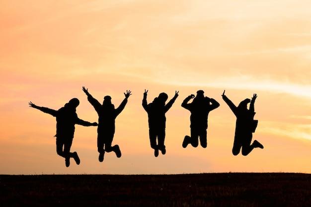 Schattenbild von den freunden, die in sonnenuntergang springen. sport und aktives lebenskonzept Premium Fotos