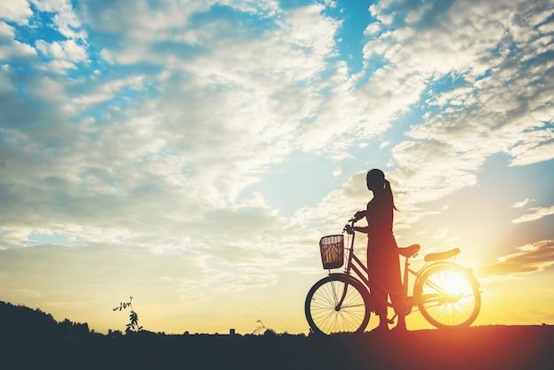 Schattenbild von frauen mit fahrrad und schönem himmel Kostenlose Fotos