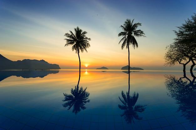 Schattenbild von kokosnussbäumen agains sonnenaufgang weg vom meer Premium Fotos