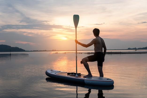 Schattenbild von stehen oben den paddelinternatsschüler, der bei sonnenuntergang auf einem flachen warmen ruhigen fluss schaufelt. Premium Fotos