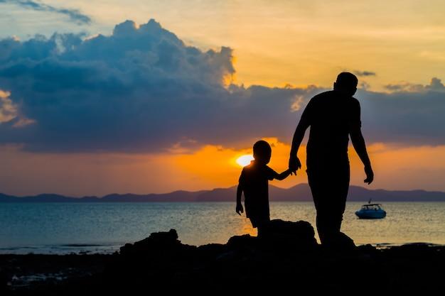 Schattenbildbild des vaters und des sohns am strand vor sonnenunterganghintergrund Premium Fotos
