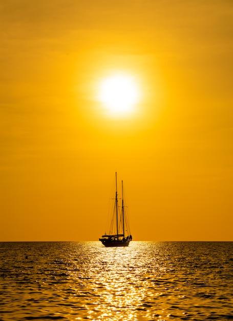 Schattenbildboot im meer und im ozean mit schönem sonnenunterganghimmel Premium Fotos