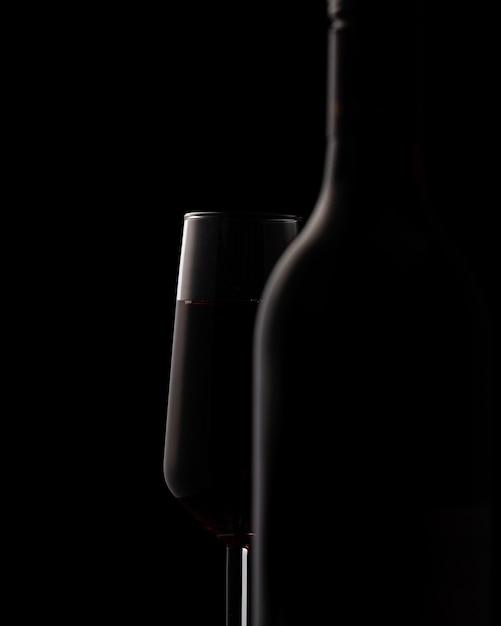 Schattenbilder der weinflasche und des weinglases auf schwarzem Kostenlose Fotos