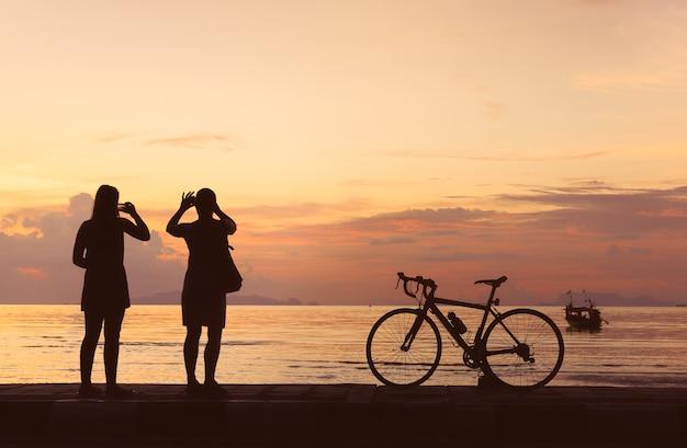 Schattenbildfahrrad und -leute machen foto am strandsonnenunterganghintergrund Premium Fotos