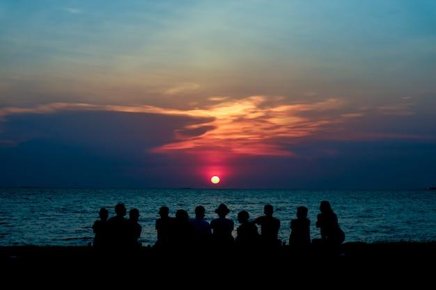 Schattenbildfamilienblick letzten hellen sonnenunterganghimmel auf dem strand Premium Fotos