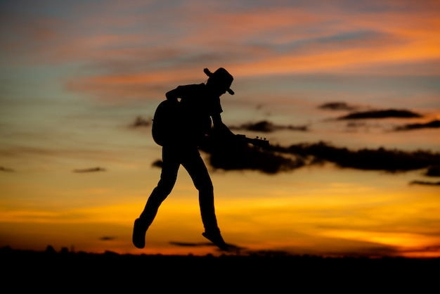 Schattenbildmädchengitarrist auf einem sonnenuntergang Kostenlose Fotos