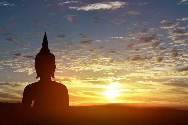 Schattenbildstatue von buddha am sonnenunterganghintergrund Premium Fotos