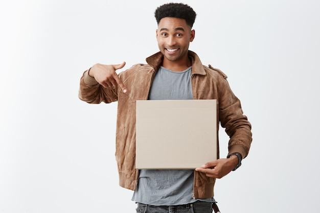 Schau dir das an. schließen sie herauf porträt des jungen schönen schwarzhäutigen männlichen universitätsstudenten mit afro-frisur in der stilvollen herbstkleidung, die auf karton in händen mit glücklichem ausdruck zeigt Kostenlose Fotos