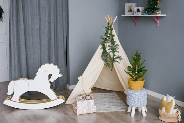 Schaukelpferd in einem kinderzimmer dekoriert für weihnachten Premium Fotos