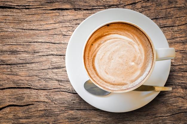 Schaumiger schaum des heißen kaffeecappuccino latte in der weißen schale auf altem holztisch Premium Fotos
