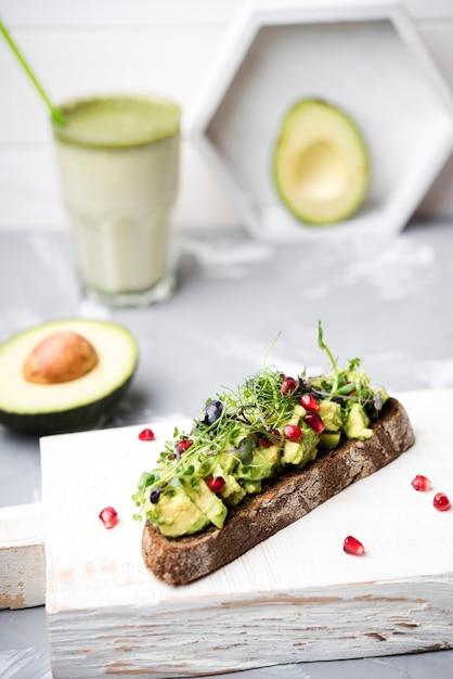Scheibe brot mit avocado-nudeln und einem glas smoothie Kostenlose Fotos