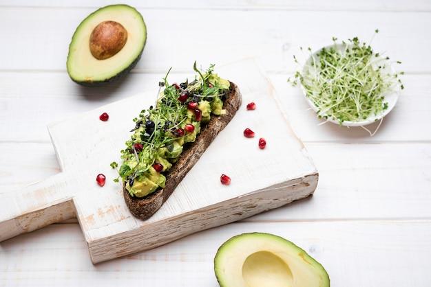 Scheibe brot mit hoher ansicht der avocadoteigwaren und des granatapfels Kostenlose Fotos