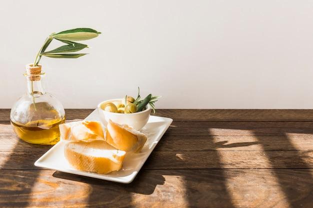 Scheibe brot mit schüssel oliven auf behälter über dem holztisch gegen wand Kostenlose Fotos