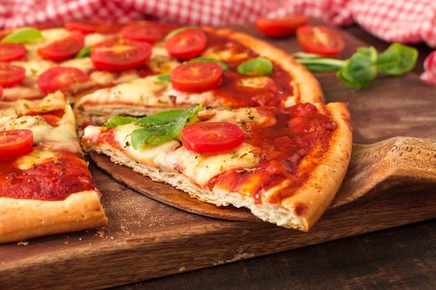 Scheibe der köstlichen pizza auf hölzerner spachtel Kostenlose Fotos
