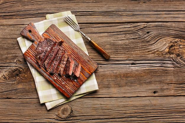 Scheibe des gegrillten steaks auf schneidebrett mit gabel und serviette über tabelle Premium Fotos