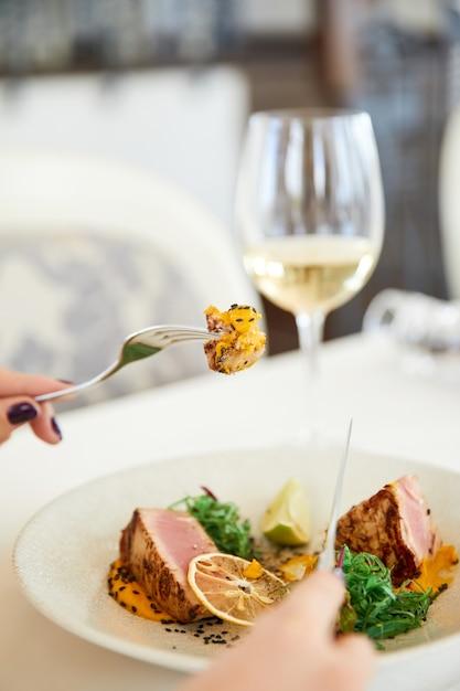 Scheibe einer leckeren thunfischmahlzeit mit einem glas weißwein im restaurant Kostenlose Fotos