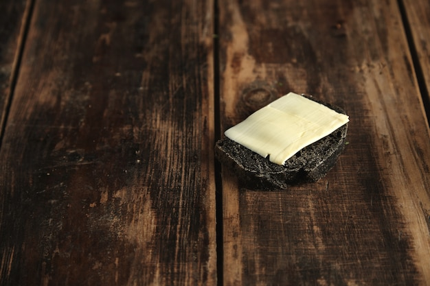 Scheibe schwarzes holzkohle luxus hausgemachtes brot mit butter isoliert auf rustikalen holztisch Kostenlose Fotos