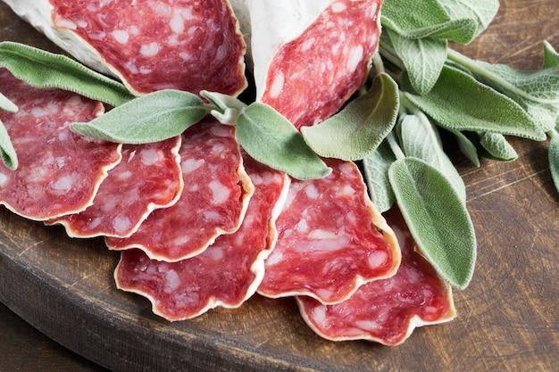 Scheiben der französischen käse-getrockneten salami mit gewürzen auf hölzernem hintergrund Premium Fotos