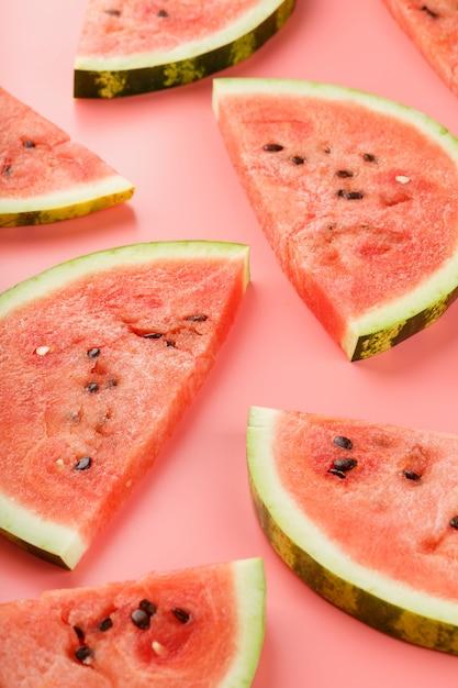 Scheiben der roten wassermelone auf rosa hintergrund in der form. Premium Fotos