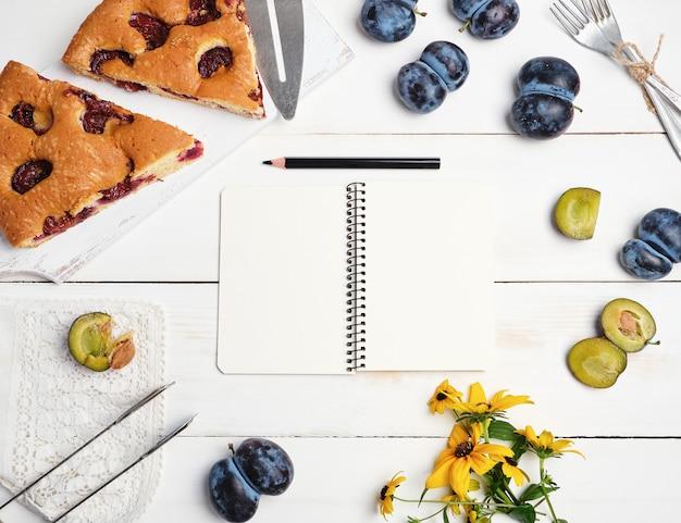 Scheiben des kekspflaumenkuchens auf einem weißen hölzernen brett und frischen früchten Premium Fotos