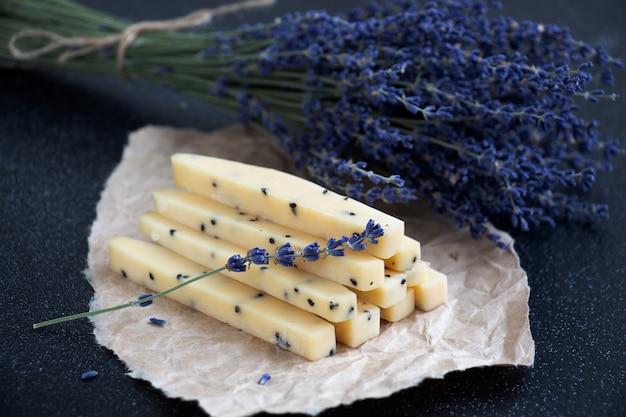Scheiben des lavendelkäses mit zweigen des lavendels auf pergamentpapier mit einem dunklen hintergrund Premium Fotos