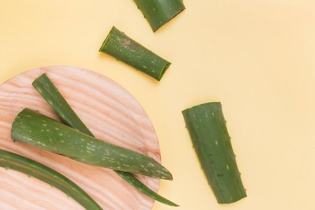 Scheiben von aloe vera verlässt auf hölzerner platte über dem gelben hintergrund Premium Fotos