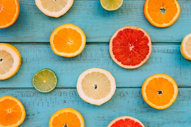 Scheiben von frischen saftigen zitrusfrüchten auf blauer hölzerner planke Kostenlose Fotos