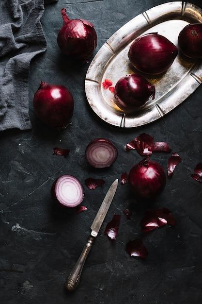 Scheiben von roten zwiebeln auf einem schwarzen schmutzhintergrund Kostenlose Fotos