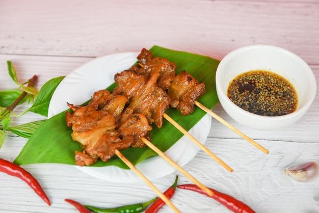 Scheibenschweinefleischaufsteckspindelstöcke grillten bananenblatt auf weißer platte mit soßenpaprikaknoblauch - gegrillte thailändische asiatische straßenlebensmittelart des schweinefleisch Premium Fotos