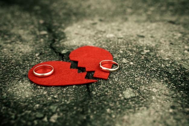 Scheidungskonzept - gebrochenes herz mit eheringen auf gebrochenem asphalt Premium Fotos