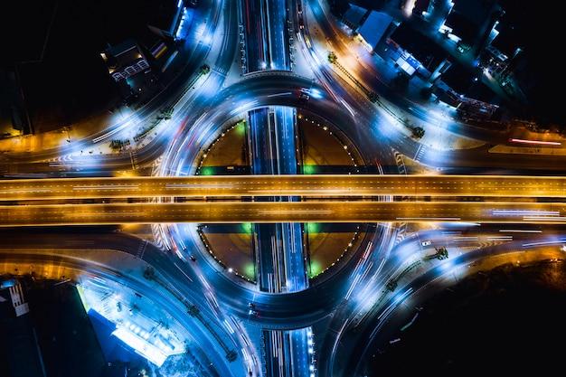 Scheinwerferauto des langen belichtungsnachtverkehrs auf dem ringstraßen- und autobahnüberführungsschnitt, der das stadttransport-logistikgeschäft in thailand anschließt Premium Fotos