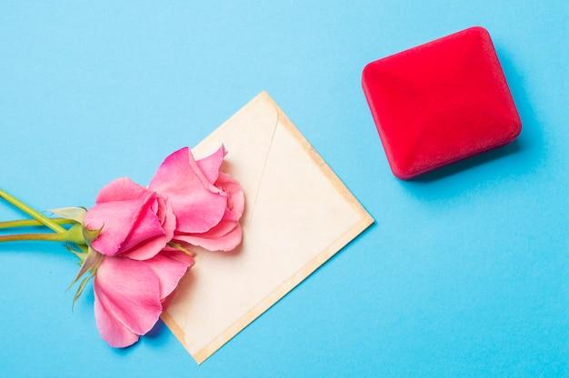 Schellen sie in einem kasten mit einem umschlag und rosen auf einem blauen hintergrund Premium Fotos