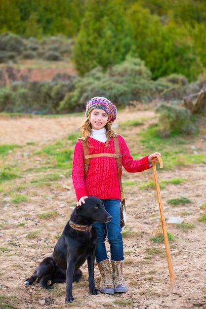 Scherzen sie die mädchenhirtein, die mit hund und schafherde glücklich ist Premium Fotos
