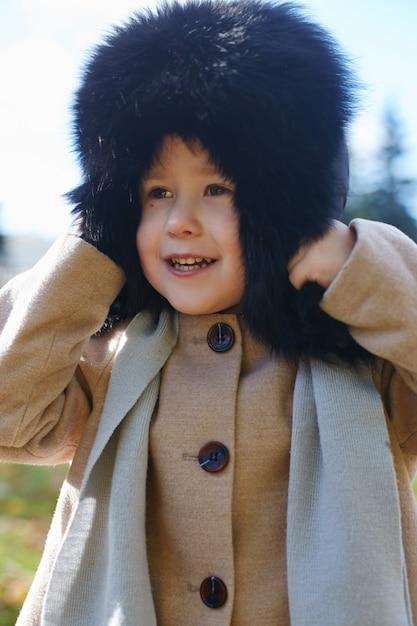 Scherzt baby in der retro- herbstfrühlingskleidung. kleines kind sitzt lächelnd in der natur Premium Fotos