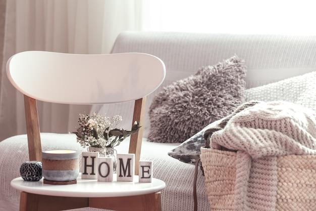 Schickes interieur für ein haus. kerzen, eine vase mit blumen mit holzbuchstaben des hauses auf weißem holzstuhl. sofa und weidenkorb mit kissen im hintergrund. haus dekoration. Kostenlose Fotos