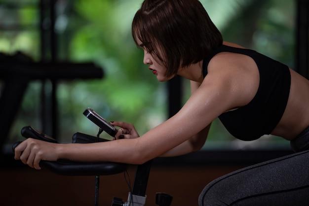 Schieben sie die ansicht der eignungsfrau trainierend mit dem laufen auf tretmühlenmaschine in der turnhalle. Premium Fotos