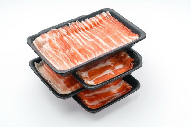 Schieben von rohem schweinefleisch auf weißem hintergrund. Kostenlose Fotos