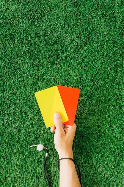 Schiedsrichterkonzept mit der hand, die karten hält Kostenlose Fotos