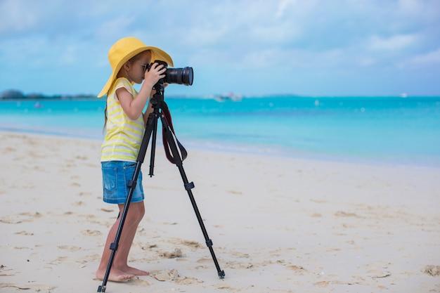 Schießen des kleinen mädchens mit kamera auf einem stativ während ihrer sommerferien Premium Fotos