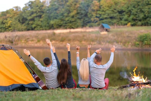Schießen sie von hinten, eine gruppe glücklicher freunde, die am flussufer kampieren, hände hochhalten und die aussicht genießen, urlaubsspaß Premium Fotos