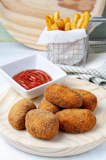 Schinken-hähnchen-kroketten mit pommes frites und tomaten Premium Fotos