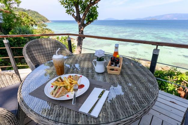 Schinkensandwich mit gemüse, pommes-frites und eiskaffee auf holztisch am patio der seeansicht Premium Fotos