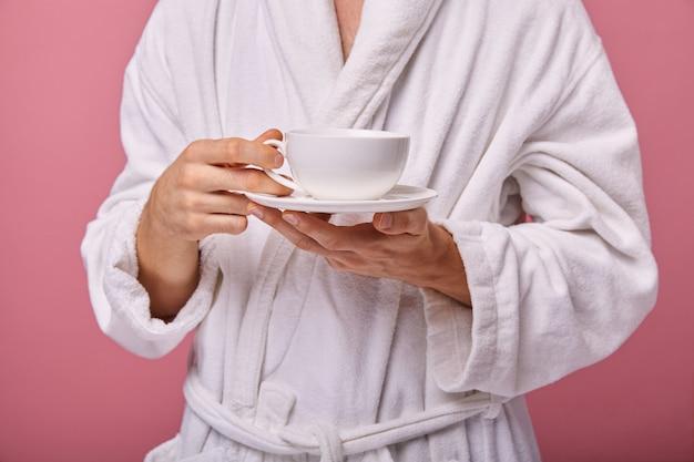 Schläfriger junger mann mit tasse kaffee in seinen händen Premium Fotos