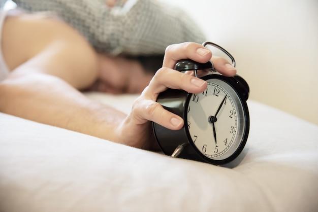 Schläfriger mann, der den wecker hält Kostenlose Fotos