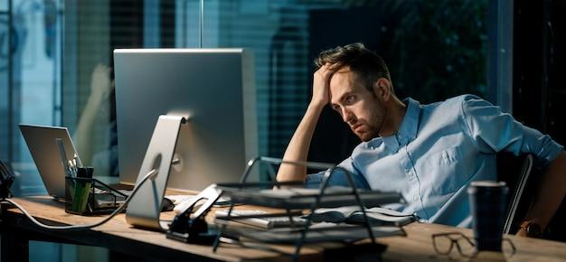 Schläfriger mann, der stundenlang im büro arbeitet Premium Fotos