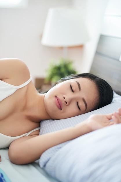 Schlafende asiatische frau auf dem bett Kostenlose Fotos