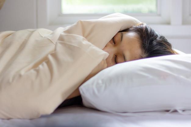 Schlafendes gesicht der jungen frau beim lügen im weißen bett in der sonnenstrahldämmerung. Premium Fotos